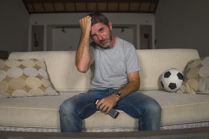 Partido de fútbol de observación triste y frustrado joven del hombre del aficionado al fútbol en la televisión en el sofá de la s imagen de archivo libre de regalías