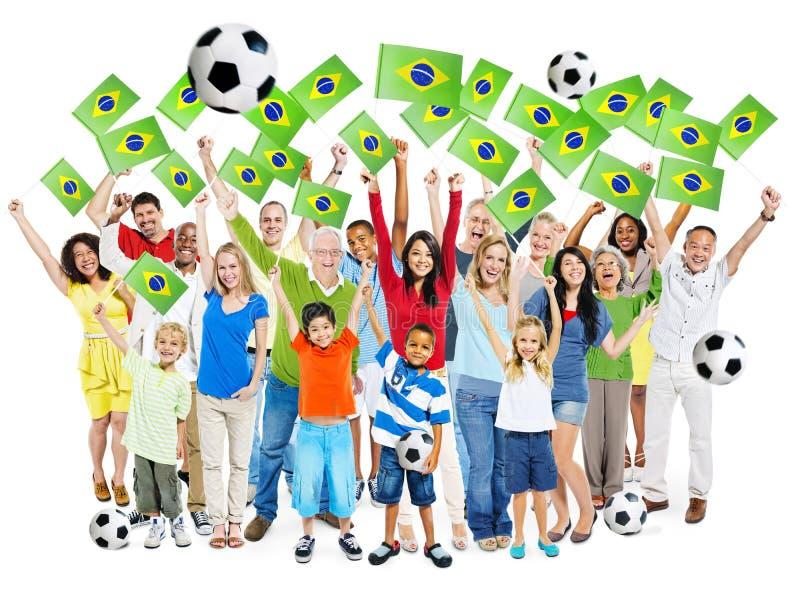 Partido de fútbol que anima de la gente con la bandera del Brasil imagen de archivo