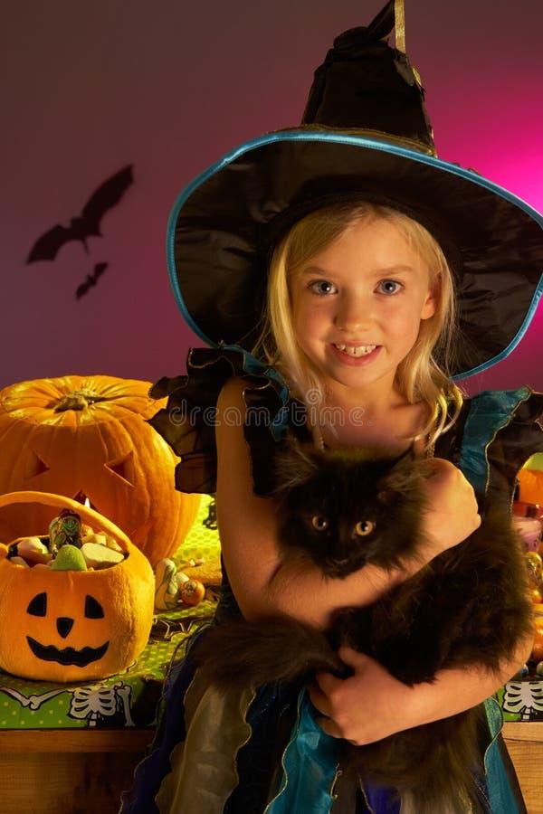 Partido de Halloween com uma criança que prende o gato preto fotos de stock royalty free