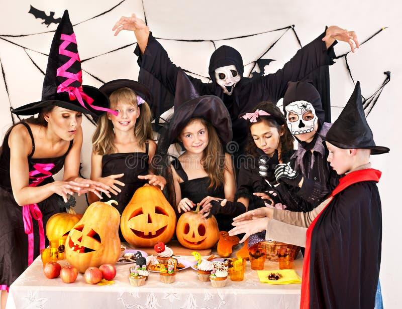 Partido de Halloween con los niños que llevan a cabo truco o la invitación. imagen de archivo libre de regalías