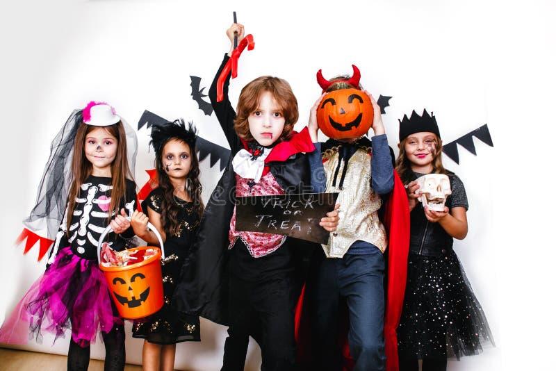 Partido de Halloween Crianças engraçadas em trajes do carnaval no fundo branco foto de stock royalty free