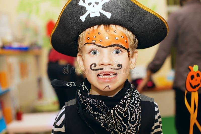 Partido de Halloween Um rapaz pequeno em um traje do pirata e em uma composição o foto de stock royalty free