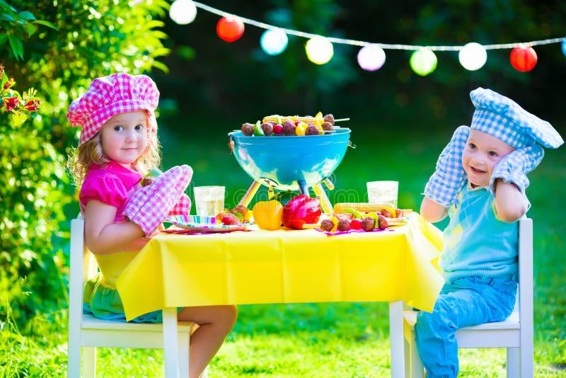 Partido de la parrilla del jardín para los niños imagen de archivo
