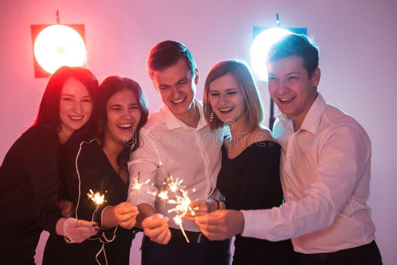 Partido del Año Nuevo, celebración y concepto de los días de fiesta - hombres jovenes y mujeres alegres que sostienen bengalas ar fotos de archivo