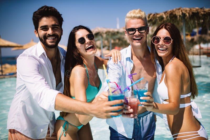 Partido del verano Amigos en los coctails de la playa y la diversión de consumición el tener foto de archivo libre de regalías