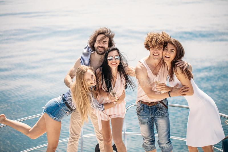 Partido del yate con la gente joven que tiene un partido del barco, bailando en un arco de la cubierta del yate imagen de archivo
