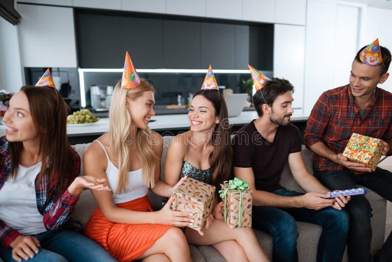Partido en honor del cumpleaños Los individuos y las muchachas se están sentando en el sofá y están teniendo conversación fotografía de archivo libre de regalías