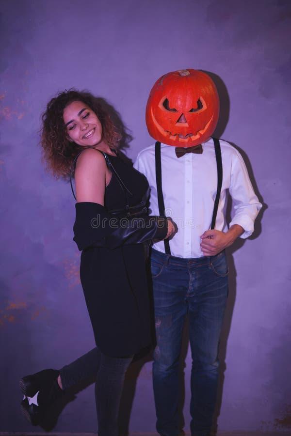 Partido inusual de Halloween de los pares Hombre con la calabaza tallada en la cabeza foto de archivo