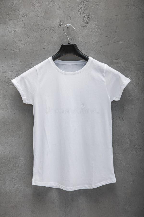Partie antérieure de T-shirt blanc femelle de coton sur un cintre photos stock
