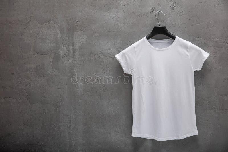 Partie antérieure de T-shirt blanc femelle de coton sur un cintre et un mur en béton à l'arrière-plan T-shirt sans copie et copys photographie stock libre de droits