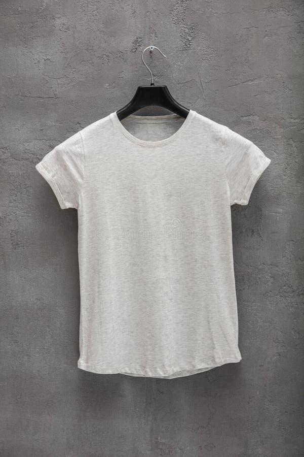 Partie antérieure de T-shirt gris femelle de coton de mélange sur un cintre et un mur en béton à l'arrière-plan image stock