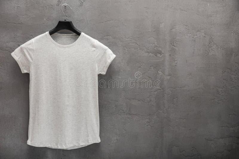Partie antérieure de T-shirt gris femelle de coton de mélange sur un cintre et un mur en béton à l'arrière-plan photo stock