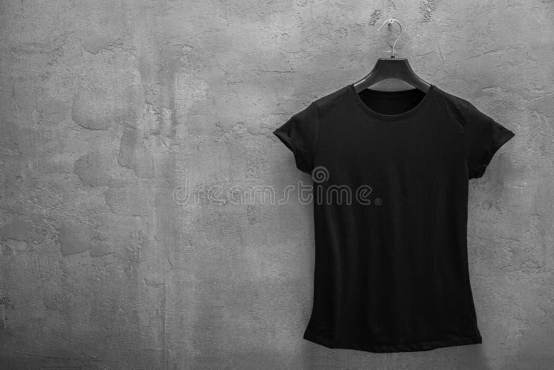 Partie antérieure de T-shirt noir femelle de coton sur un cintre et un mur en béton à l'arrière-plan photos stock