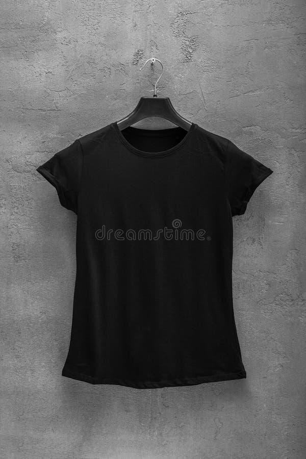 Partie antérieure de T-shirt noir femelle de coton sur un cintre et un mur en béton à l'arrière-plan photo stock