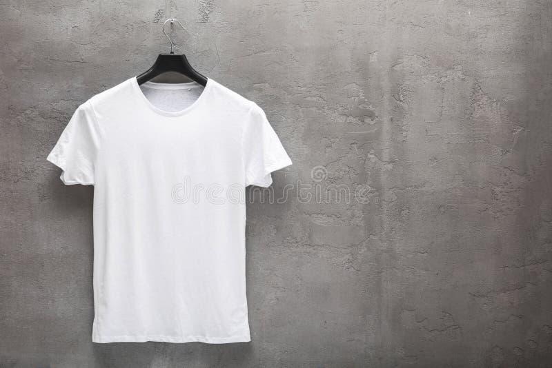 Partie antérieure du T-shirt blanc masculin de coton sur un cintre images libres de droits