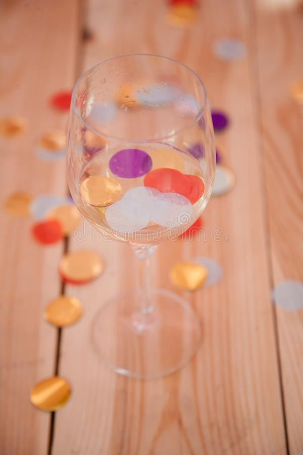 Partie au-dessus des confettis vides en verre de vin de fond image stock