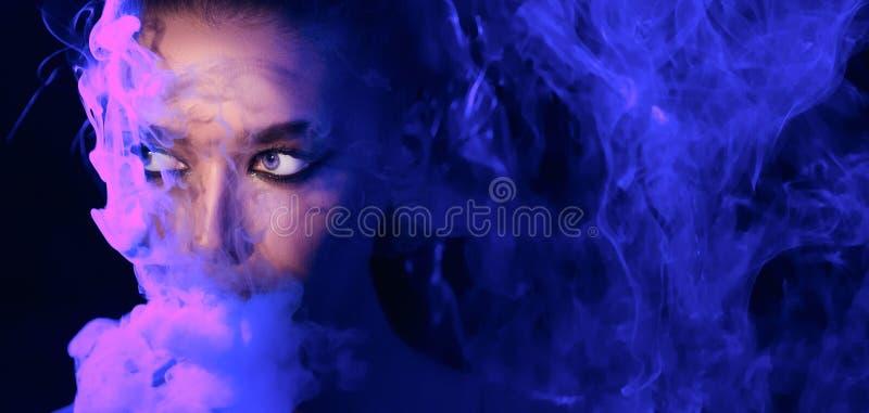 partie au n?on Femme vaping dans le club, fumée illuminée par les lampes au néon photo stock
