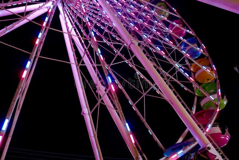 Partie d'une grande roue allumée la nuit avec les gondoles multicolores images libres de droits