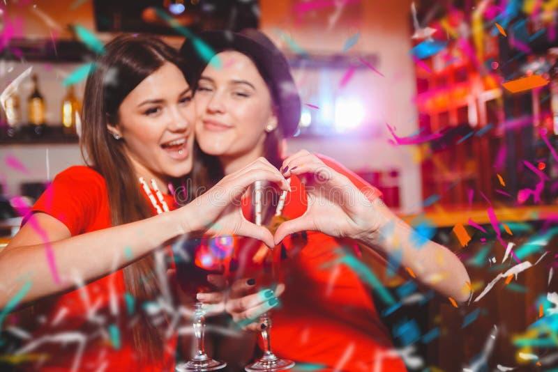 Partie de confettis Deux jeunes filles lesbiennes font un coeur avec leurs mains ? une partie de club image libre de droits
