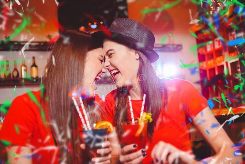 Partie de confettis Deux lesbiennes de jeunes filles à une partie dans le club photographie stock libre de droits