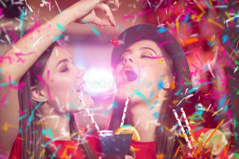 Partie de confettis Deux lesbiennes de jeunes filles à une partie dans le club tiennent des cerises de cocktail photo stock
