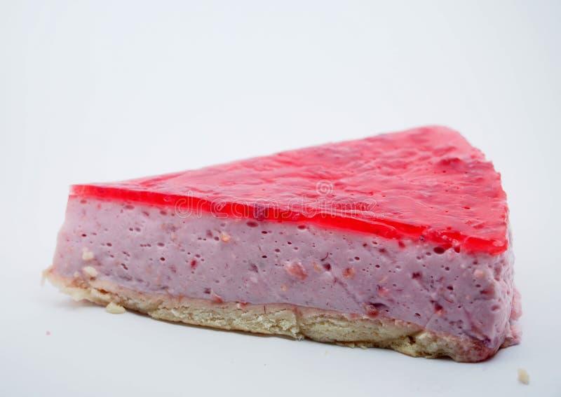 Partie de gâteau sur le fond blanc Gâteau au fromage avec la gelée de framboise image stock