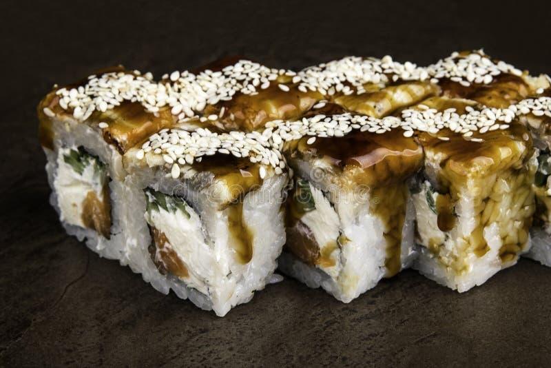 Partie de petits pains de style japonais avec de la sauce foncée et vue de côté des graines de sésame sur un fond foncé images libres de droits