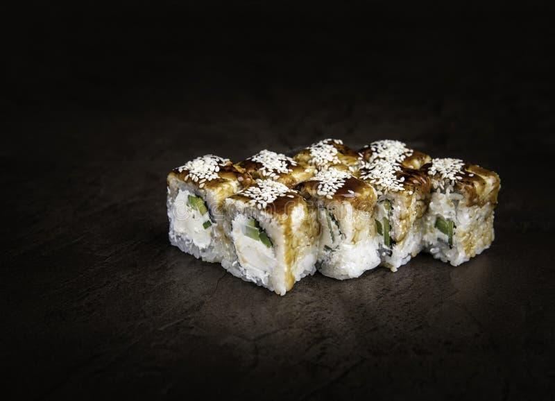 Partie de Rolls de style japonais avec le fromage à pâte molle et le concombre sur un espace foncé de copie de fond image libre de droits