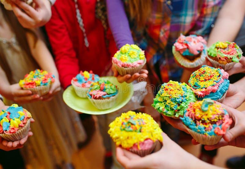 partie du ` s d'enfant Enfants tenant des petits gâteaux dans les verres photo stock