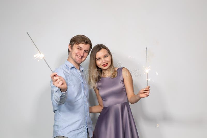 Partie, famille et concept de vacances - jeune couple regardant aux cierges magiques sur le fond blanc image stock