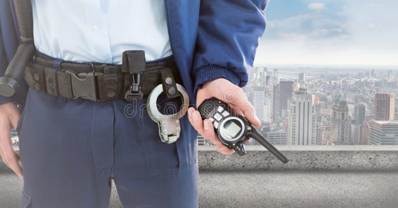 Partie inférieure du corps de garde de sécurité avec le talkie-walkie contre l'horizon photo stock