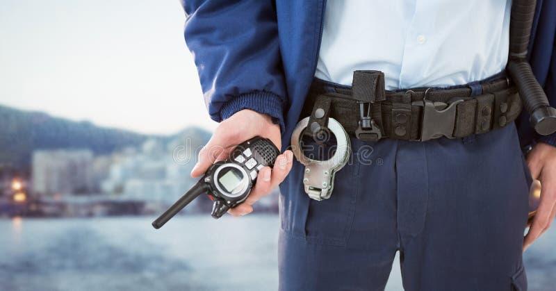 Partie inférieure du corps de garde de sécurité avec le talkie-walkie contre l'horizon trouble image stock