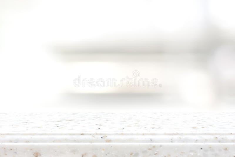 Partie supérieure du comptoir en pierre blanche sur le fond d'étagère de tache floue image libre de droits