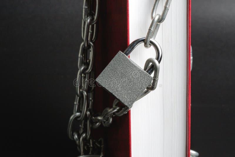 Partie verticalement debout du livre sur lequel accroche un cadenas de chaîne en métal, livre rouge photos stock