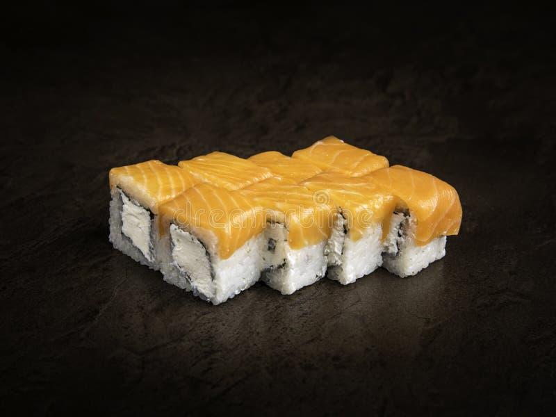 Parties de petits pains de style japonais avec le fromage à pâte molle et la truite sur un fond foncé image libre de droits