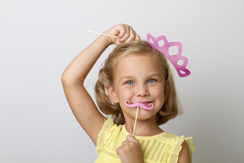 Partiet för flickainnehavpapper klibbar på en fast bakgrund royaltyfria bilder