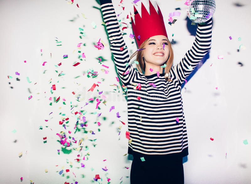 Partiflickan i färgrika strålkastare och konfetti som ler på vit bakgrund som firar brightful händelse, bär avrivet arkivbilder