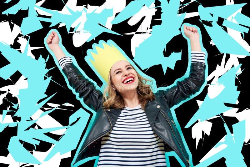 Partiflickan i läderomslag och partikronan på pastell slösar bakgrund som firar och dansar Parti och att ha gyckel arkivfoto