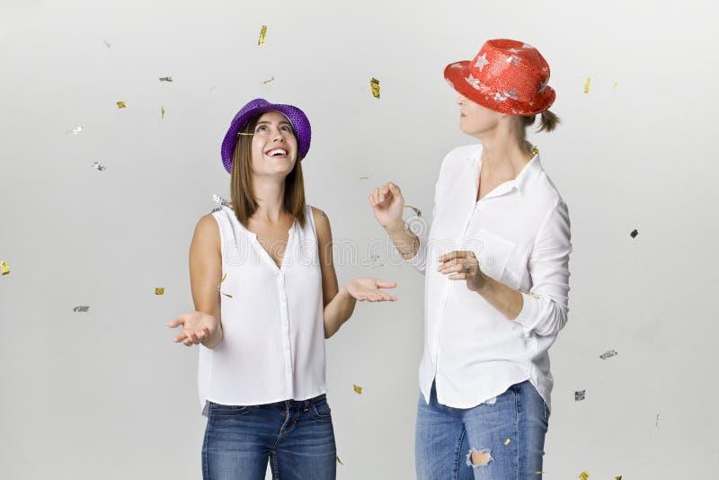 Partiflickvänner med konfettier och färgrika hattar Det är avkoppling- och danstid arkivbilder