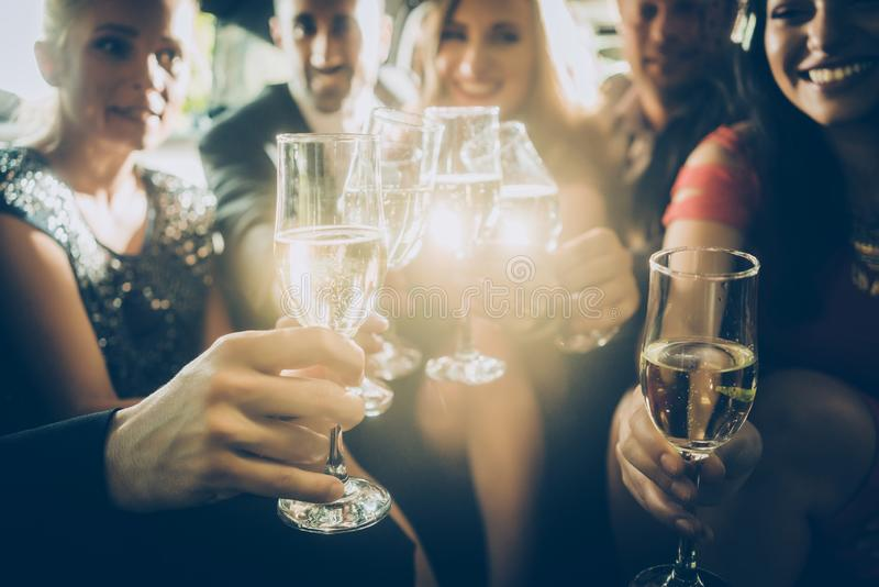 Partifolkmassa som klirrar exponeringsglas med champagne royaltyfria foton