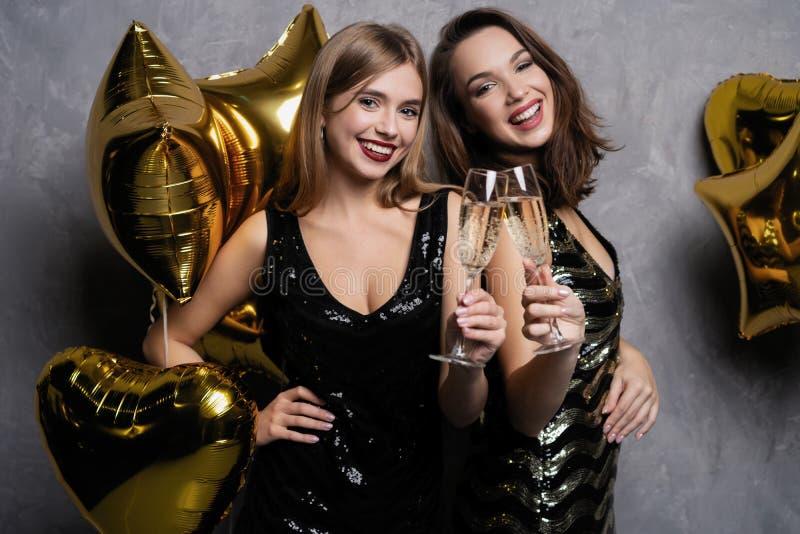 Partigyckel härliga fira flickor isolerade nytt över det vita året Stående av ursnygga le unga kvinnor som tycker om partiberöm royaltyfria bilder