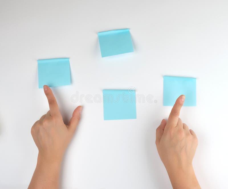 partij die van blauwe stickers op een witte achtergrond en twee vrouwelijke handen op hen richten stock afbeeldingen