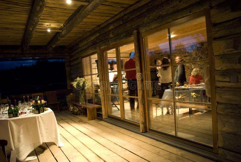 Partij in een plattelandshuisje bij nacht stock afbeelding