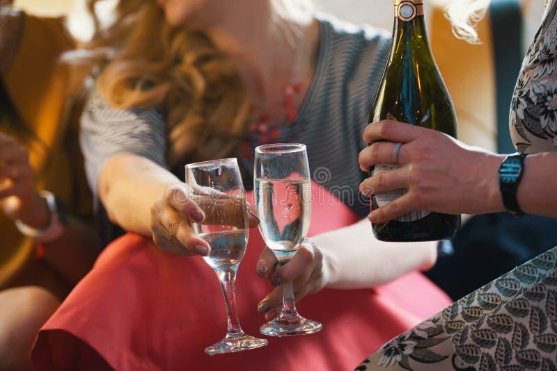 Partij in limousine - gelukkige meisjes die, drinkt de vrouwen champagne de vieren - sluit omhoog stock afbeeldingen