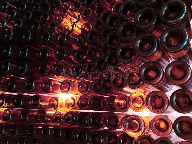 partij van de flessen van het wijnglas op een muur en indirect licht in oranje kleur, achtergrond en textuur royalty-vrije stock afbeelding