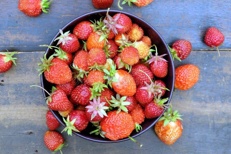 Partij van rijpe smakelijke aardbeien in de ronde kom op uitstekende houten lijstclose-up stock foto