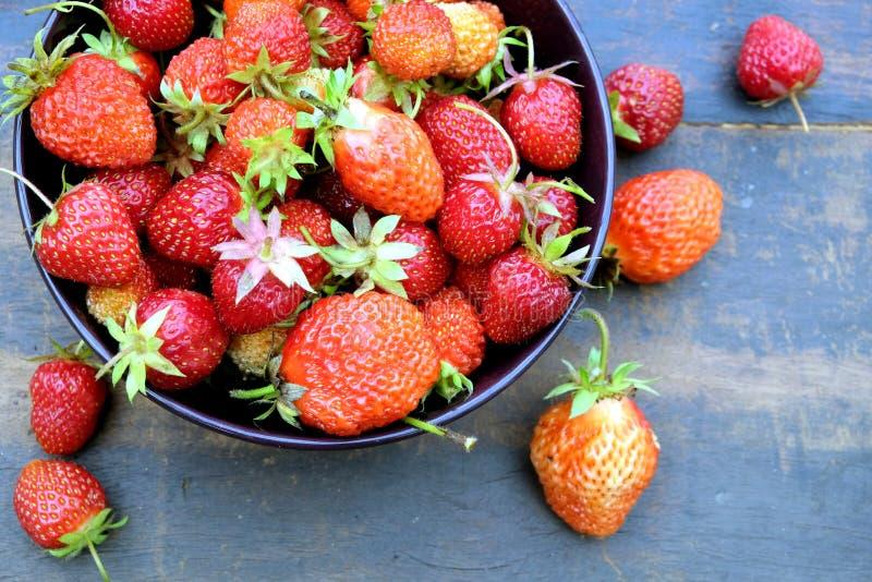 Partij van rijpe smakelijke aardbeien in de ronde kom op uitstekende houten lijstclose-up royalty-vrije stock foto