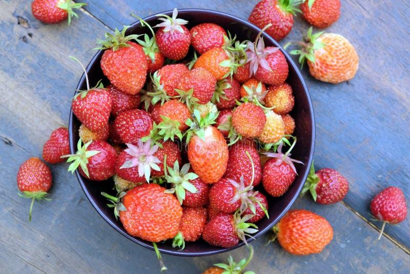Partij van rijpe smakelijke aardbeien in de ronde kom op uitstekende houten lijstclose-up stock afbeeldingen