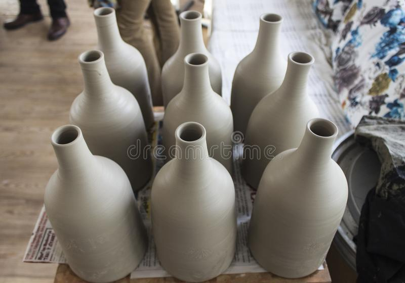 Partij van traditioneel met de hand gemaakt flessenontwerp van grijs kleuren ruw ceramisch materiaal na gekookt stock foto