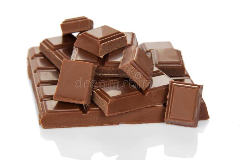 Partijen smakelijk van stukken van gebroken die melkchocola op wit worden geïsoleerd stock foto